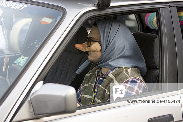 Man dressed as a witch behind the wheel of a car  part of a carnival (Mardi Gras) parade in Schwabmuenchen  Swabia  Bavaria  Germany  Europe