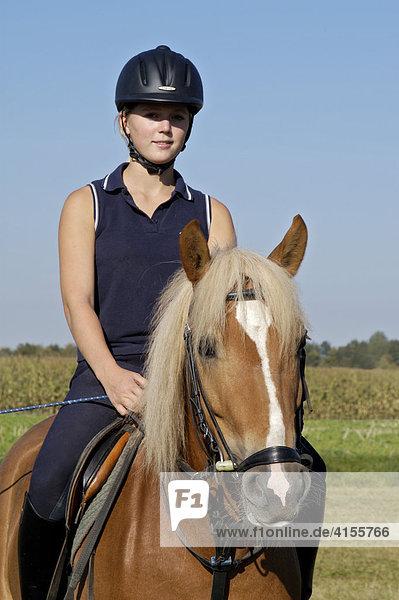 Junge Reiterin mit Reithelm auf Haflinger