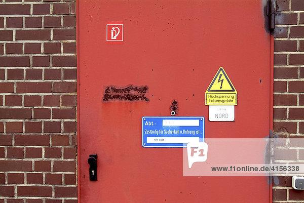 Hinweistafeln rot  gelb  blau und weiss auf roter Tür