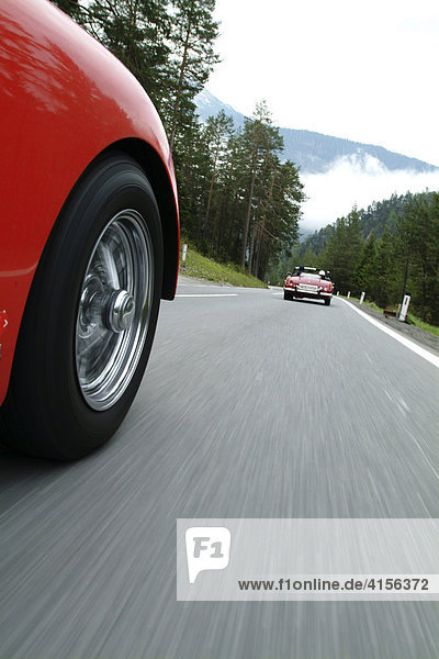 Roter TR 3 von aussen waehrend er Fahrt hinter roten Oldtimer