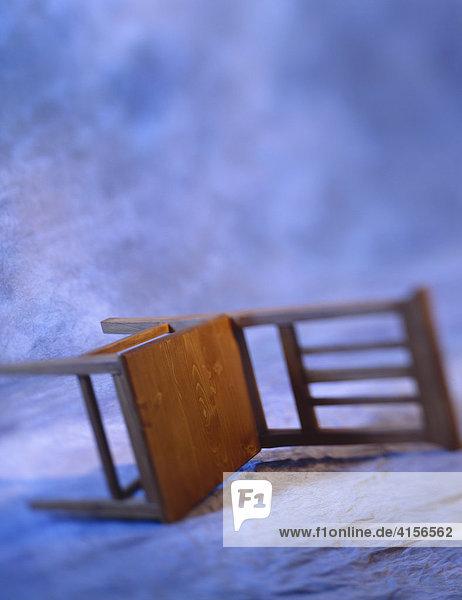 Umgekippter Stuhl auf blauem Hintergrund