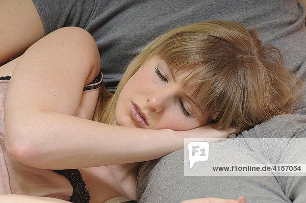 Paar schläft auf Couch