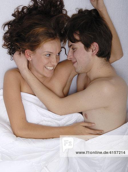 Liebespaar im Bett sieht sich in die Augen und lacht