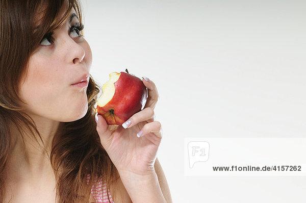Hübsche junge braunhaarige Frau isst einen roten Apfel