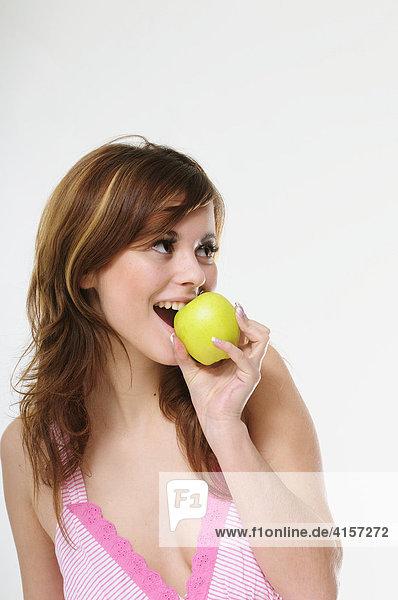 Hübsche junge braunhaarige Frau isst einen grünen Apfel