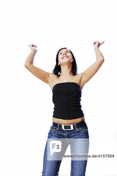 Schwarzhaarige Frau vor weißem Hintergrund tanzt
