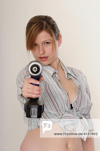 Junge  langhaarige Frau mit Hemd bauchfrei mit Bohrmaschine