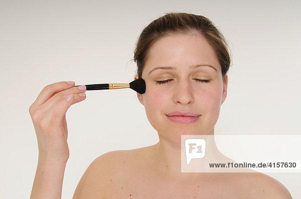 Junge Frau pudert Gesicht