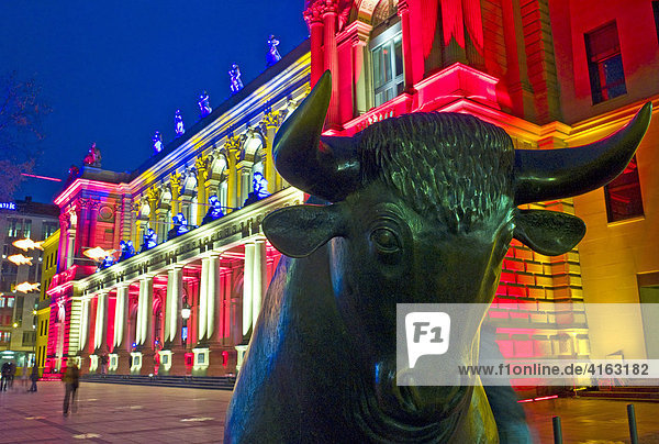 The bull of the Bull and Bear in front of the brightly lit Frankfurt Stock Exchange at night,  illuminated by multicoloured spotlights for the Luminale,  biannual lighting festival in Frankfurt,  Germany