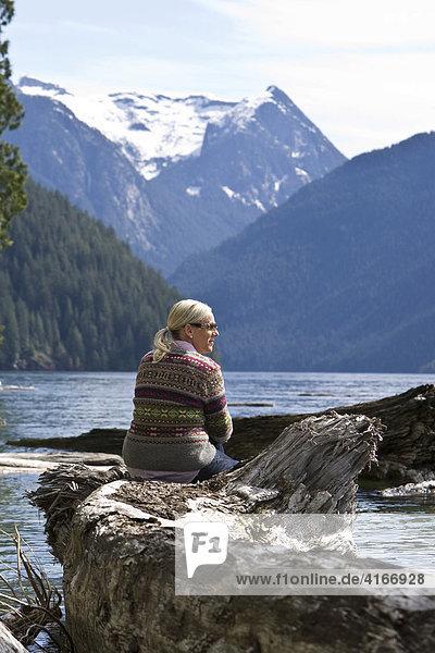 Frau sitzt am Ufer des Pitt Lake  British Columbia  Kanada  Nordamerika