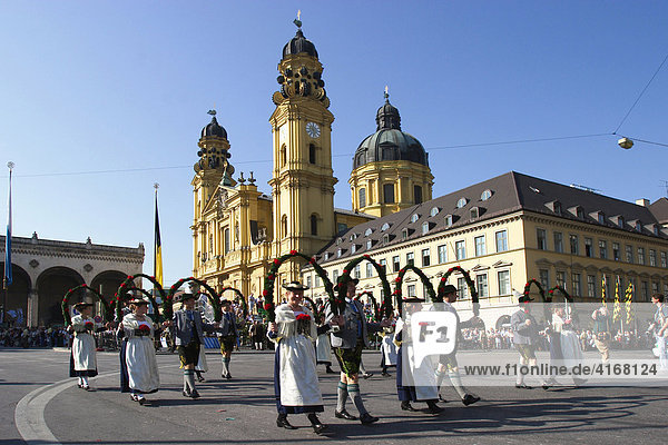 Trachten- und Schützenzug zu Beginn vom Oktoberfest in München - im Hintergrund die Theatinerkirche