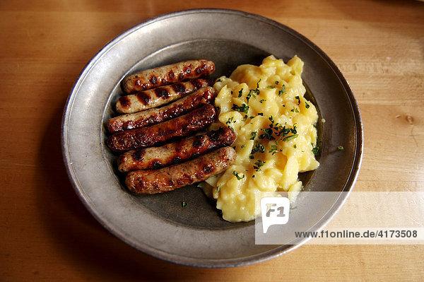 6 Nürnberger Bratwürstchen mit Kartoffelsalat auf einem Zinnteller  Nürnberg  Mittelfranken  Bayern  Deutschland  Europa 6 Nürnberger Bratwürstchen mit Kartoffelsalat auf einem Zinnteller, Nürnberg, Mittelfranken, Bayern, Deutschland, Europa