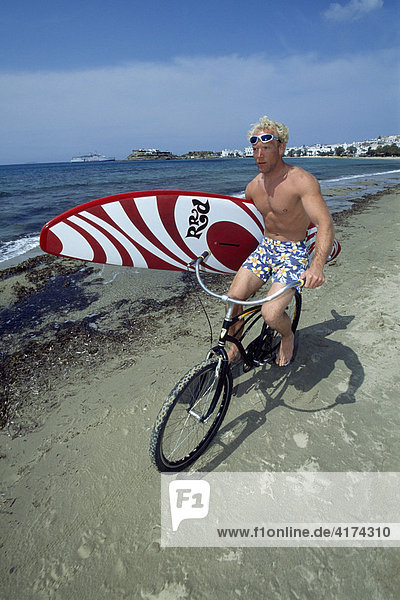 Surfer on a bicycle  Naxos Island  Cyclades  Greece
