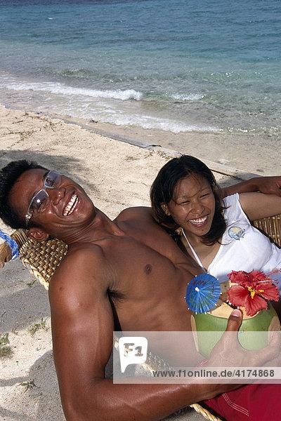 Filipinos am Strand mit einem Früchtedrink