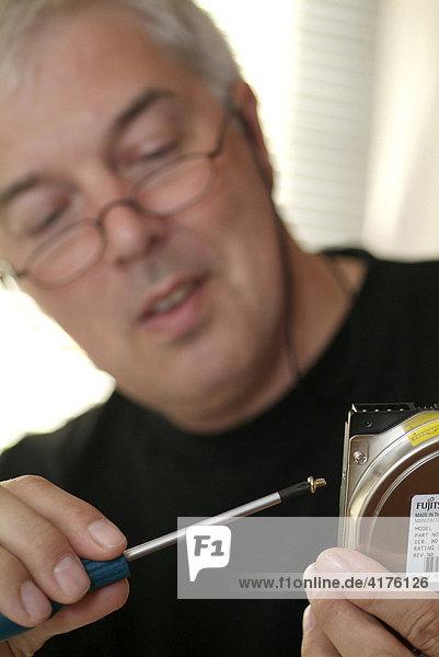 Man screws screws in harddisk