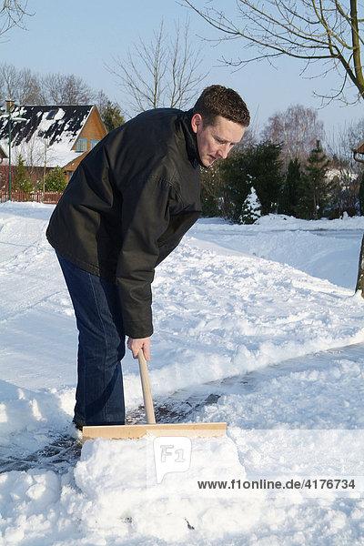 Mann schiebt schnee vom fussweg