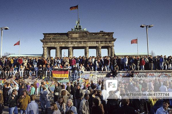 Fall der Berliner Mauer: Menschen aus Ost- und West-Berlin sind auf die Mauer am Brandenburger Tor geklettert. Berlin  Deutschland Fall der Berliner Mauer: Menschen aus Ost- und West-Berlin sind auf die Mauer am Brandenburger Tor geklettert. Berlin, Deutschland
