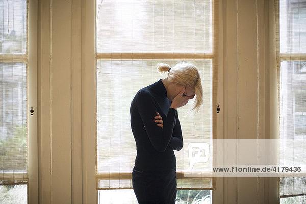 Traurige blonde Frau vor großen Fenstern