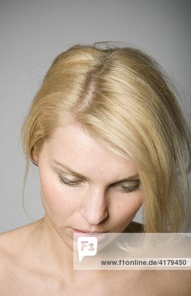 Portrait einer traurigen jungen blonden Frau mit gesenktem Kopf