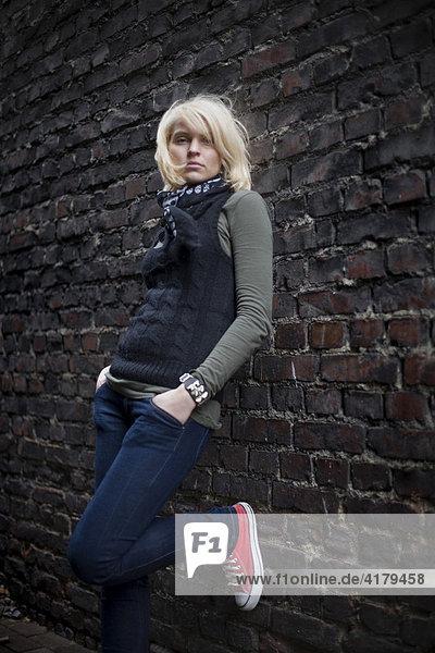Blonde Frau steht vor einer Steinmauer