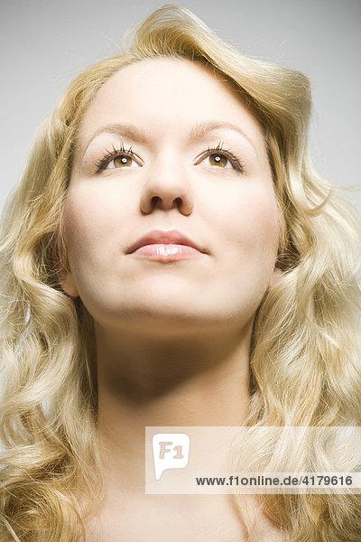 Blonde junge Frau schaut nach oben
