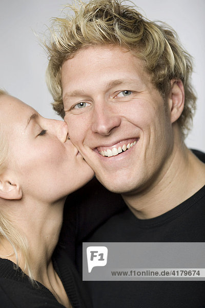 Frau küsst Mann auf die Wange