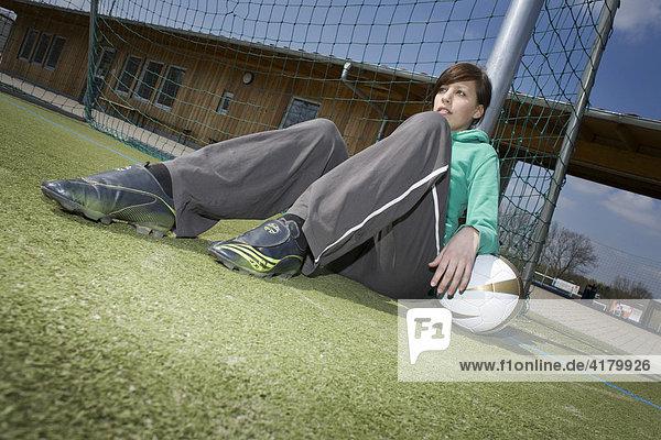 Junge Frau sitzt mit einem Fußball an einem Torpfosten gelehnt