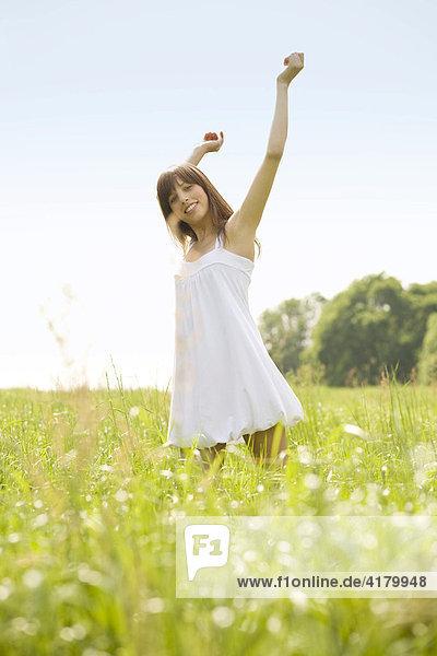 Junge dunkelhaarige Frau in einem weißen Kleid dreht sich mit ausgestreckten Armen auf einer sommerlichen Wiese