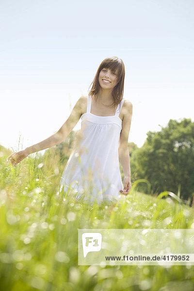 Junge dunkelhaarige Frau in einem weißen Kleid steht auf einer sommerlichen Wiese und blickt freundlich in die Kamera