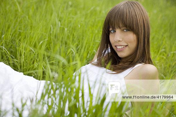 Junge dunkelhaarige Frau in einem weißen Kleid liegt entspannt auf einer Wiese  genießt den Sommer  blickt lächelnd in die Kamera