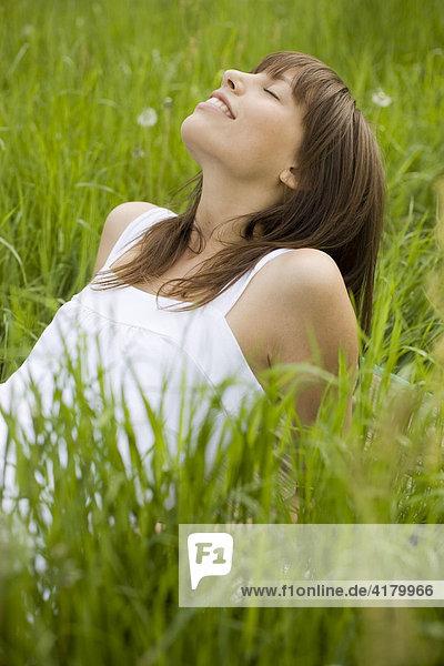 Junge dunkelhaarige Frau in einem weißen Kleid liegt entspannt auf einer Wiese  genießt den Sommer