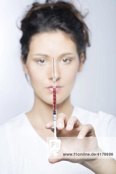 Junge Frau mit weißem Laborkittel hält eine Spritze mit roter Flüssigkeit in den Händen und blickt in die Kamera
