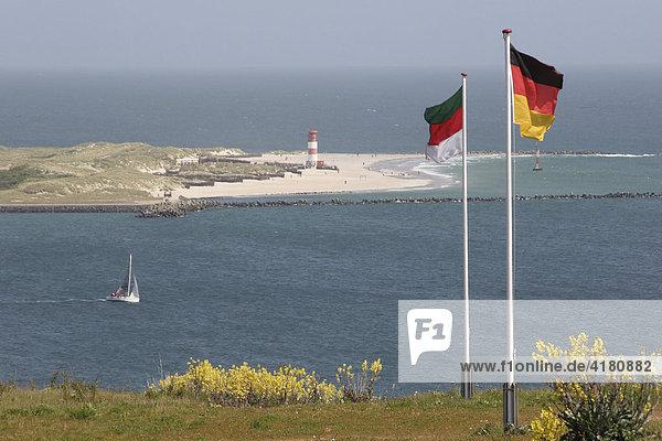 Deutsche Fahnen  ein Segelboot und die Strandinsel Düne vor der Hochseeinsel Helgoland  Schleswig-Holstein  Deutschland  Europa