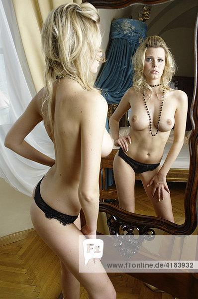 Junge Frau in erotischer Pose in einer Hotelsuite vor altem Spiegel