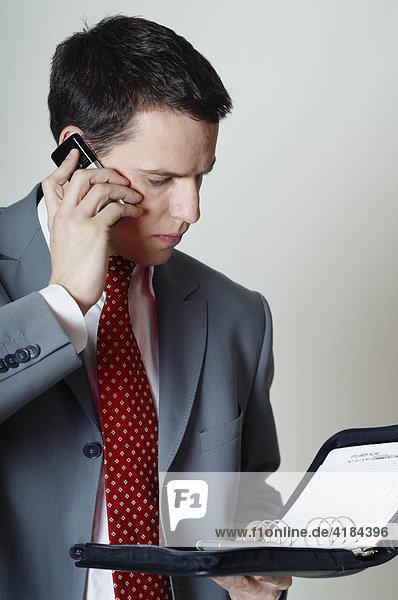 Junger Geschäftsmann Business Mann telefoniert mit Handy  schaut ins Terminbuch