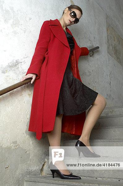Junge Frau mit Sonnenbrille und rotem Mantel im Treppenhaus