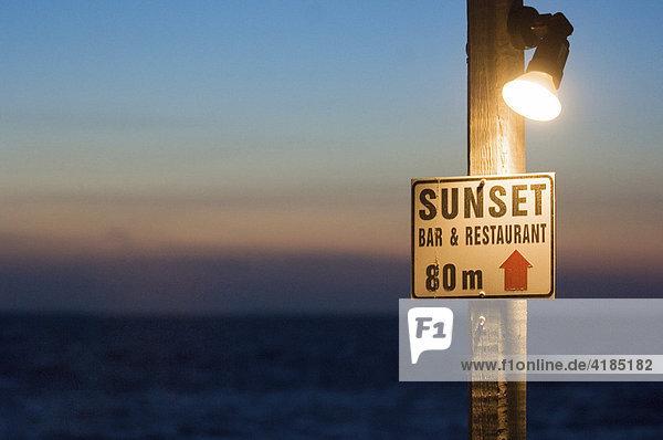 Sonnenuntergang in achtzig Metern. Hinweisschild auf eine Bar am Ufer  von der aus man den Sonnenuntergang beobachten kann  Griechenland