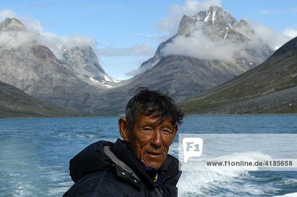 Portrait Inuit  Grönländer  im Qinngertivaq Fjord vor hohen Bergen  Solporten  Ostgrönland  Grönland  Arktis