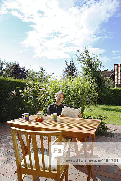Lesender Mann im Garten