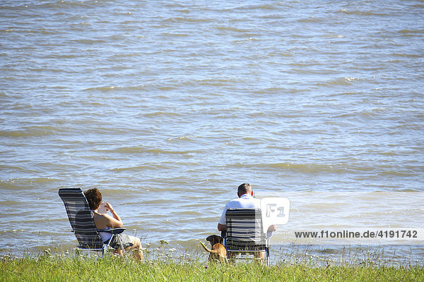Couple sitting near the water  mouth of the Weser River  Lower Saxony  Germany  Europe