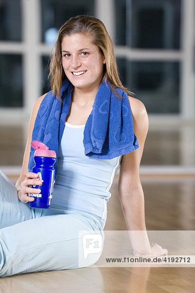 Eine junge Frau nach dem Training mit einer Powerdrink-Flasche in der Hand