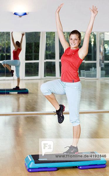 Eine junge Frau trainiert mit einem Stepper