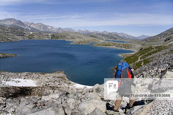 Wanderer in Gebirgslandschaft  See  Schnee  Crater Lake  Chilkoot-Trail  Britisch Columbien  Kanada