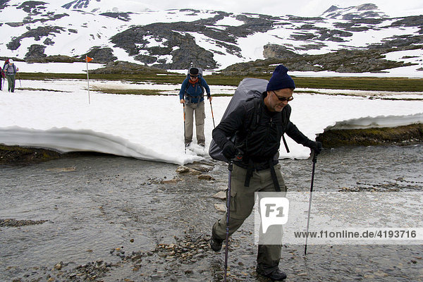 Hiker crossing stream  thaw  mountain landscape  Chilkoot Trail  British Columbia  Canada