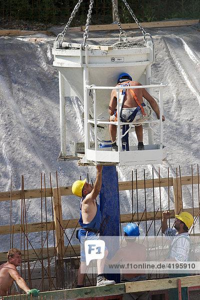 Bauarbeiter mit Betonbehälter auf einer Großbaustelle