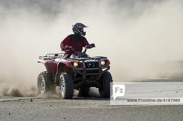 Quad drives on dusty piste