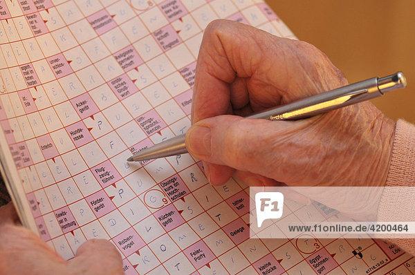 Seniorin löst Kreutzworträtsel