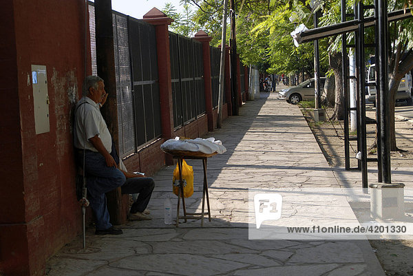 Old man selling traditional baked goods  chipa or bread  on the pavement  Ciudad Formosa  Formosa Province  Argentina  South America