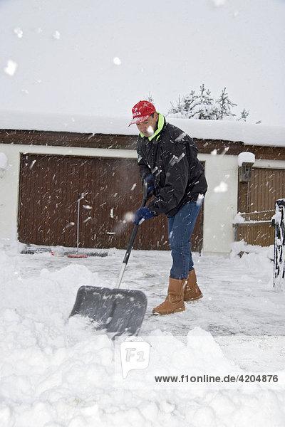 Mann beim Schneeschaufeln vor Garageneinfahrt bei Schneetreiben