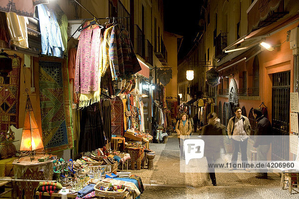 Teahouses  tourists and souvenir shops selling Moroccan handicrafts at night in the colourful Caldereria Nueva street  Granada  Andalusia  Spain